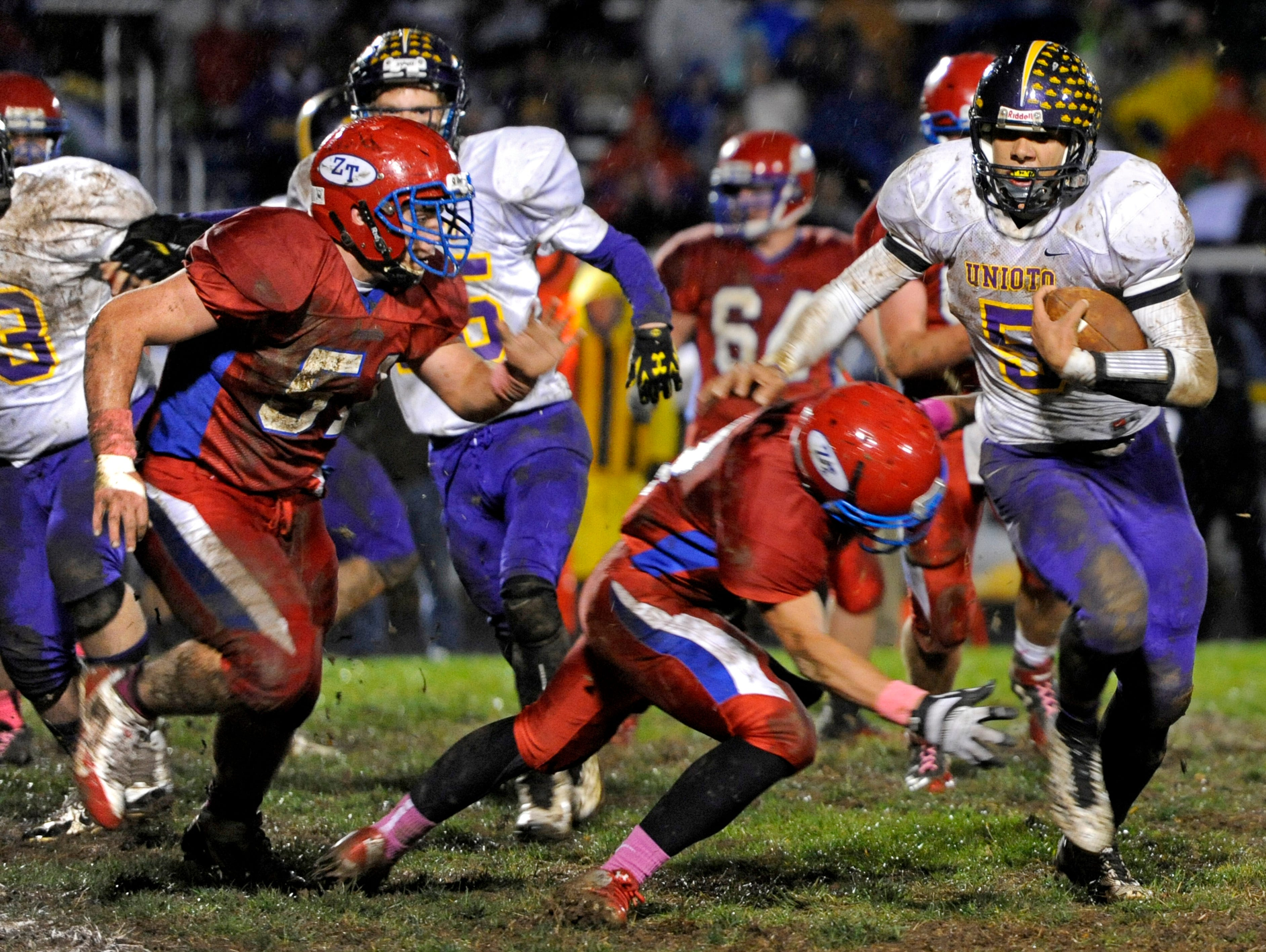 Unioto's Erique Hosley tries to break a tackle before being brought down by Zane Trace defenders during the second quarter of Friday's game.