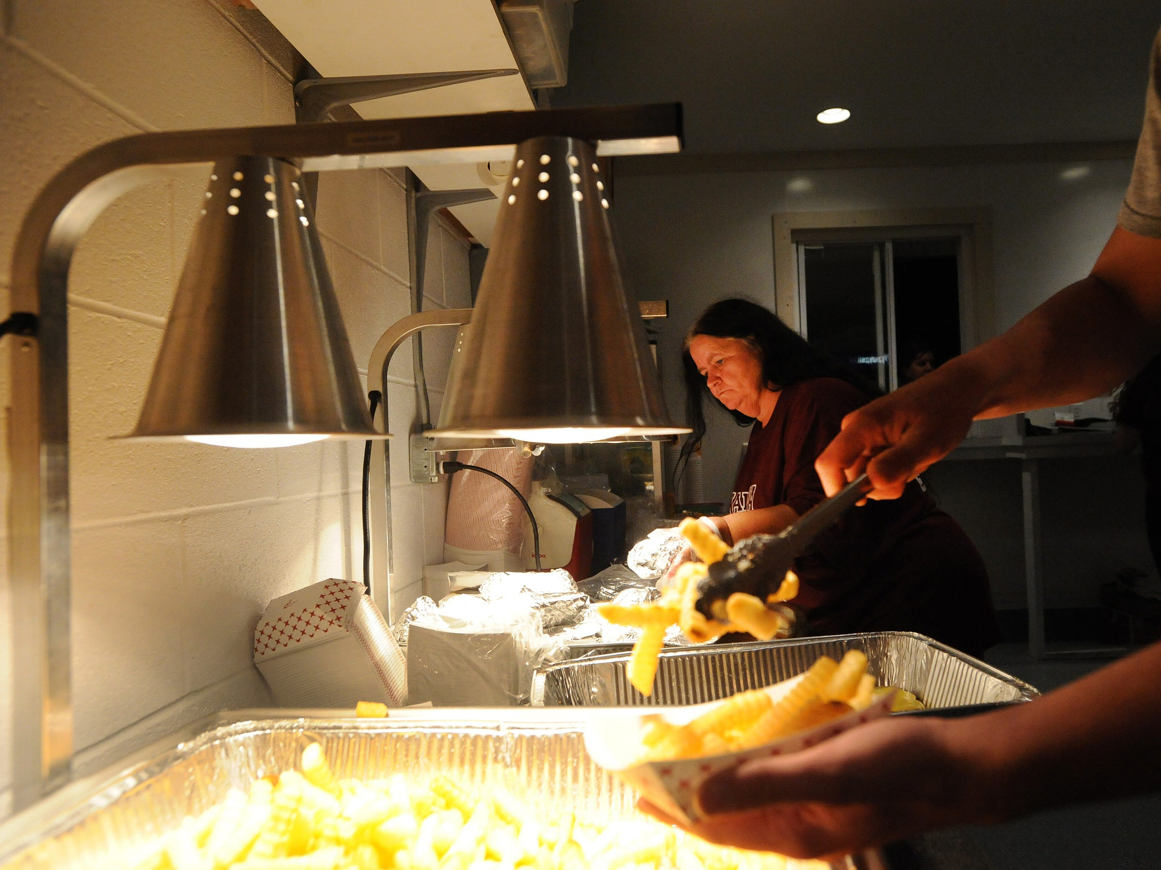 Betty Colona preps burgers for customers in the Nandua concession stand during halftime of a game on Friday, Oct. 3, 2014.