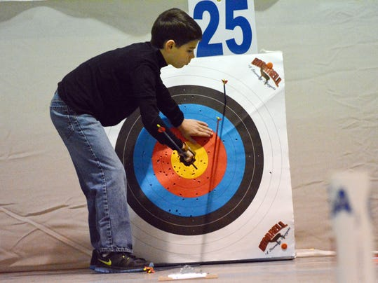 ANI Archery Tournament Randon Wooley, a student at J.I. Barron Elementary School, pulls his arrows after scoring. Wooley and about 550 area students participated in the Cenla Shootout south regional tournament at the LSU AgCenter's State Storm Shelter at L