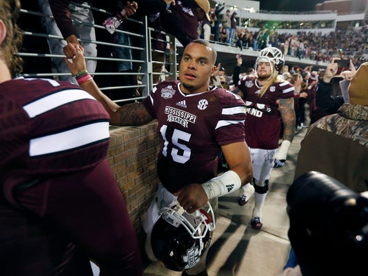 Mississippi State quarterback Dak Prescott (15) thanks fans following their victory over Arkansas in their NCAA college football game in Starkville, Miss., Saturday, Nov. 1, 2014. No. 1 Mississippi State won 17-10. (AP Photo/Rogelio V. Solis)