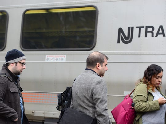 Commuters board a NJ Transit train in this file photo.