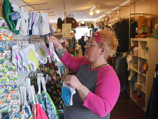 Shelly Gaddis, owner of Elegant Mommy, puts items back