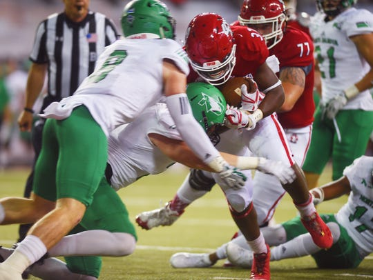 USD's Kai Henry pushes past UND's defense Saturday