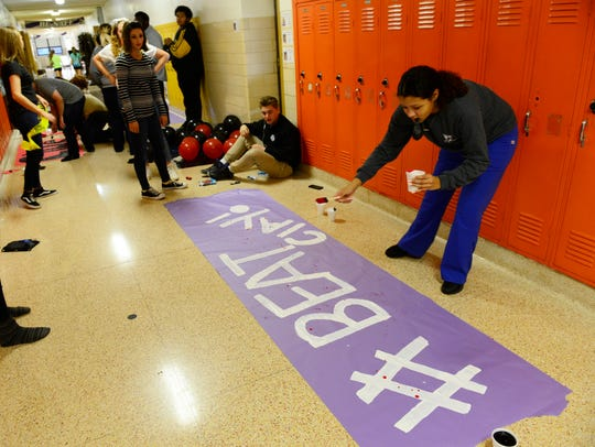 Sophomore Malayah Harper paints a banner Thursday to