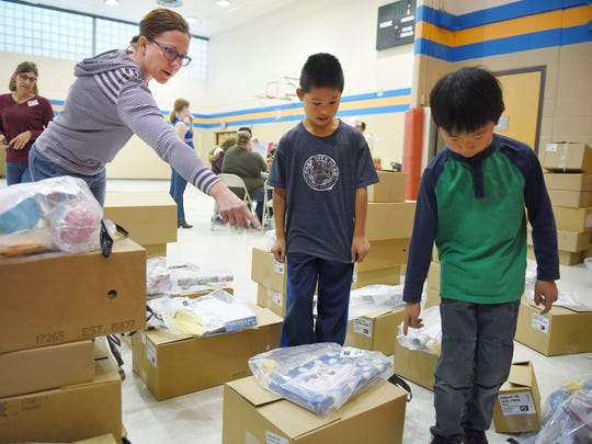 Cleveland Elementary School Parent Teacher Association member Emily Gieseke has her sons Beck and Owen help her gather packages from Club's Choice Fundraising Wednesday, Nov. 8, at the elementary school.