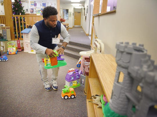Youth Care Provider Jerrone Holmes picks up toys after