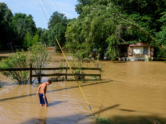 Daniel Kelley wades out into the flood waters in the morning hours after flash floods swept through low lands and creek beds at Swink Road in Medon, Tenn., Monday, July 16, 2018.