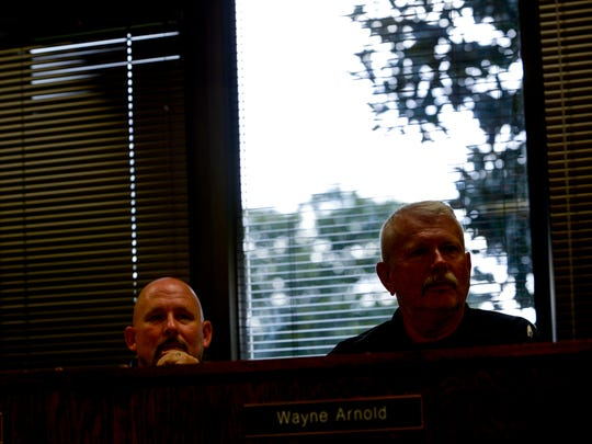 Wayne Arnold, right, and Kevin Alexander, left, listen to speakers at a board meeting at Jackson-Madison County Board of Education in Jackson, Tenn., Thursday, Aug. 9, 2018.