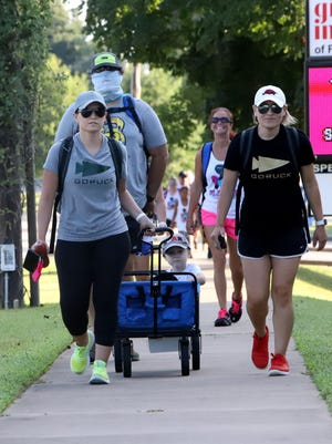 """Jane Powell, left, and Sarah Hosier lead others in the  River Valley Ruckers """"Ruck For Hope,"""" Saturday, August 1, 2020, leaving Creekmore Park on a three-mile ruck along Old Greenwood Road. All totaled, walkers carried more than 250 pounds of food stuffs in their rucksacks and backpacks for donation to the Riverview Hope Campus, a place where homeless service providers meet to offer comprehensive assistance to the homeless in our area."""