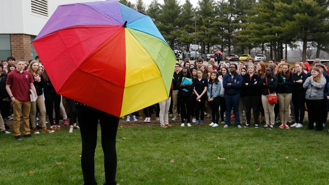Dowling Catholic freshman Saffron Edwards, 15, center, speaks to the crowd from under her rainbow-colored umbrella Wednesday during a walkout protesting the private Catholic school's decision not to hire full-time a gay teacher in Des Moines. More than 150 students, alumni and supporters gathered outside the school to protest the school's decision.