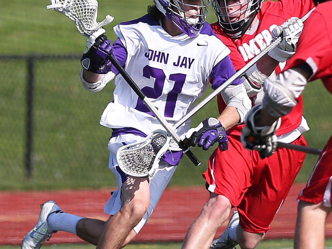John Jay's Matt Lupinacci (21) tries to get around Somers' Evan Kieltyka (10) during playoff lacrosse action at John Jay High School in Cross River May 19, 2015. John Jay won the game 12-5.