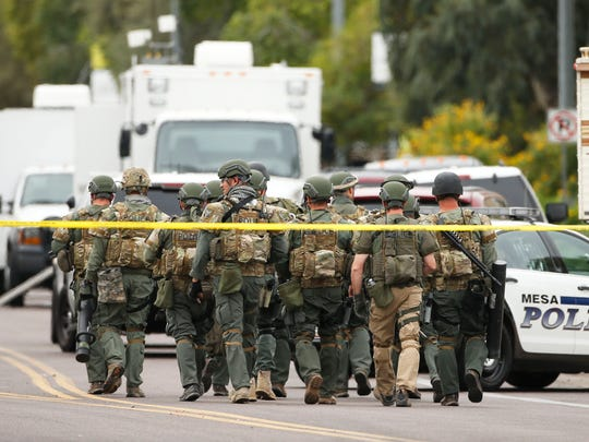 A SWAT team walks down South Longmore Road near Adams