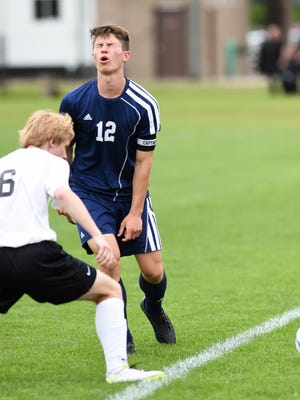 Iowa City Regina's Nicolas Ziniel (12) makes a face after he loses control of the ball and it goes out of bounds Thursday at the state soccer tournament.