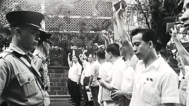 "In this photograph received from the South China Morning Post taken on May 16, 1967, protesters wave ""The Quotations From Chairman Mao Zedong"" in front of police outside the South Kowloon Magistracy in Hong Kong."