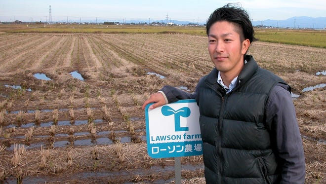 Farmer Ryusuke Goto next to harvested rice fields in Niigata, Japan