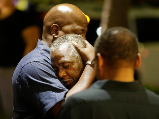 Worshipers embrace following a group prayer across the street from the scene of a shooting at Emanuel AME Church on June 17, 2015, in Charleston, S.C.