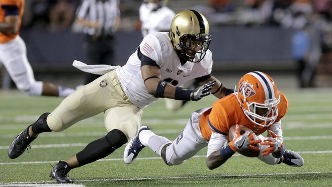 UTEP wide receiver Eddie Sinegal dives for a pass while covered tightly by Army's Elijah Riley Saturday at the Sun Bowl.
