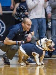 Butler Blue III, known as Trip, is Butler University's beloved bulldog mascot. He's shown with his caretaker, Michael Kaltenmark.