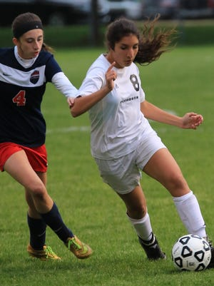 Dribbling around Livonia Franklin's Riley Hawley (No. 4) Tuesday night is Anna DeBiasi (No. 8) of Plymouth. DeBiasi scored one of four goals in the Wildcats' division-clinching win.