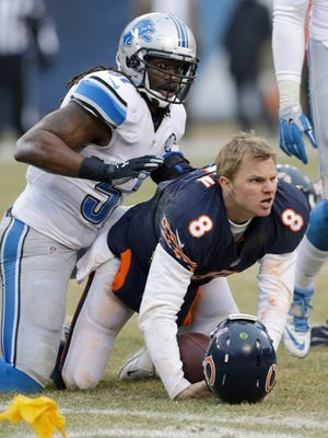 Chicago Bears quarterback Jimmy Clausen and Detroit Lions linebacker Josh Bynes, left, play Dec. 21, 2014, in Chicago.