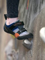 Kelli Shaffner, Geneva, works up a series of foot holds as she heads up a wall.
