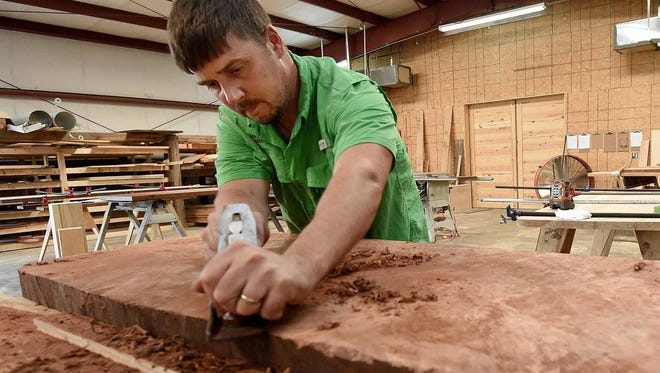 Matthew Smith, owner/artist of Deep South Wood in Canton, planes a slab of redwood burl for a live-edge coffee table.