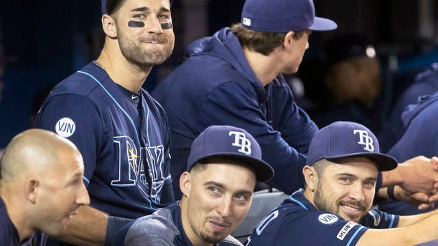 In this Sept. 28, 2019 file photo, Tampa Bay Rays' Kevin Kiermaier, top left, relaxes in the dugout with teammates in the fourth inning of a baseball game against the Toronto Blue Jays in Toronto. Major League Baseball's average salary as opening day approached remained virtually flat at around $4.4 million for the fifth straight season, according to a study of contracts by The Associated Press.