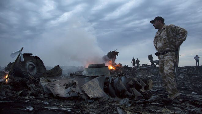 People walk amid the debris at the crash site of passenger plane MH17 near the village of Grabovo, July 17, 2014.