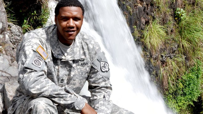 In this June 6, 2015 photo, U.S. Army National Guard Sgt. 1st Class Charleston Hartfield poses for a photo at Rainbow Falls near Hilo, Hawaii. Hartfield, was one of the people killed in Las Vegas after a gunman opened fire on Sunday, Oct. 1, 2017, at a country music festival. He worked as a Las Vegas police officer and hyouth football coach.