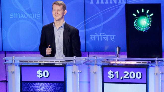 """ORG XMIT: NYR205  In this file photo of  Jan. 13, 2011, """"Jeopardy!"""" champions Ken Jennings, left, and Brad Rutter, right, look on as the IBM computer called """"Watson"""" beats them to the buzzer to answer a question during a practice round of the """"Jeopardy!"""" quiz show in Yorktown Heights, N.Y. Watson is now on a diet of medical textbooks and journals for health care. IBM says Watson, with its ability to understand plain language, can digest questions about a person's symptoms and medical history and quickly suggest diagnoses and treatments.  (AP Photo/Seth Wenig, File)"""