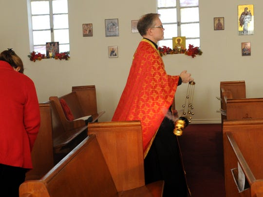 Nellie Doneva/Reporter-NewsFather Phillip LeMasters spreads incense around the church during a Christmas Eve service at St. Luke Orthodox Church Wednesday, Dec. 24, 2014.