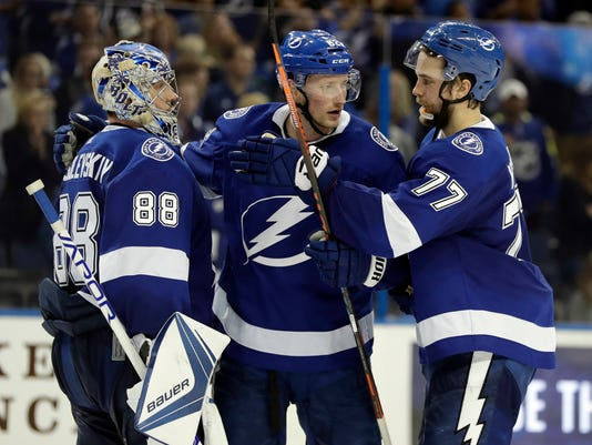 Tampa Bay Lightning goaltender Andrei Vasilevskiy (88), defenseman Andrej Sustr (62) and defenseman Victor Hedman (77) celebrate their win over the Vancouver Canucks in an NHL hockey game Thursday, Feb. 8, 2018, in Tampa, Fla. (AP Photo/Chris O'Meara)