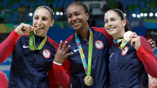 United States' Diana Taurasi, left, Tamika Catchings, center, and Sue Bird, right, celebrate with their gold medals after their win in a women's basketball game against Spain at the 2016 Summer Olympics in Rio de Janeiro, Brazil, Saturday, Aug. 20, 2016. (AP Photo/Eric Gay)