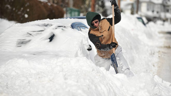 Alex Williams tries to clear snow from her buried car after a winter storm  Jan. 28 in New London, Conn.