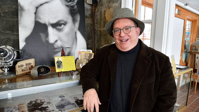 Tom Meyers, Executive Director of The Fort Lee Museum, poses with a photo of John Barrymore at the museum.