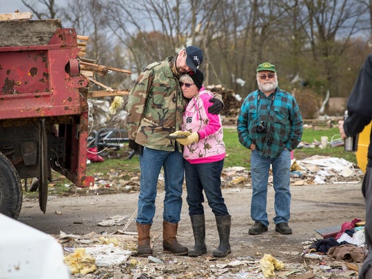Stacie Walter is embraced by her neighbor Bradley Rowles in a rubble strewn field that was once her families house. According to officials 15-20 home were severely damaged by the EF-2 tornado which swept the area.