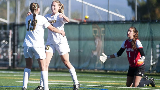Vermont's Caitie Green (10) celebrates her first goal against Maine with teammate Rylee Osgood (19) during Thursday's women's soccer game at Virtue Field.