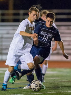 Ithaca's Tristan Cornell-Roberts maneuvers the ball around Binghamton's Ismar Turkovic on his way to scoring Ithaca's third goal in the first half of their game Wednesday evening in Ithaca. The top-ranked Little Red improved to 13-0 on the season with a 7-0 victory.