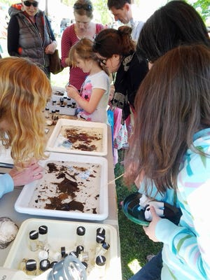 Young environmentalists enjoy an Earth Day festival soil project.