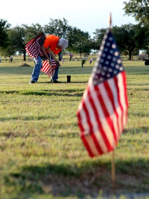 Don Nester places a flag at the gravesite of a veteran for Memorial Day at the Crestview Memorial Park cemetery Monday morning.