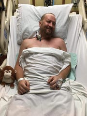 Officer Jeff Hughes smiles from his hospital bed after being diagnosed with conversion disorder syndrome.