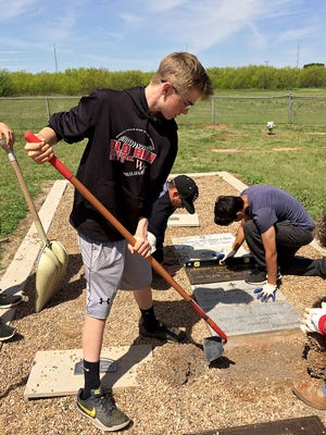 Lucas Brownfield (center) and several other Wichita Falls teens work in the Wichita County Cemetery Saturday afternoon to improve the grave markers for area veterans.
