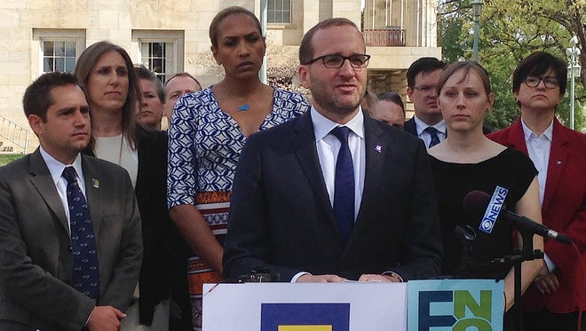 Human Rights Campaign president Chad Griffin, center, speaks at a news conference at the old state Capitol Building in Raleigh, N.C. on Thursday, March 31, 2016.