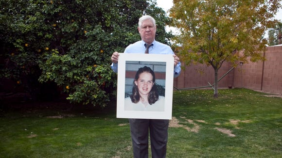Otis Smith, in his backyard,  holding a photo of his daughter, Shannon.