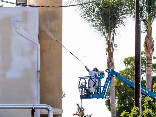 Crews prepare to paint the exterior of Tulare Regional