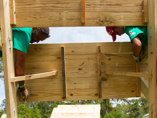 Raja Bagby, left, and his son Andrew Bagby work on a new picnic table on Saturday at Camp Caloosa in North Fort Myers.