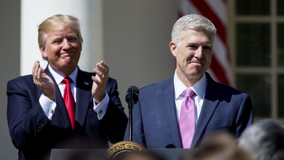 Justice Neil Gorsuch speaks as President Trump looks