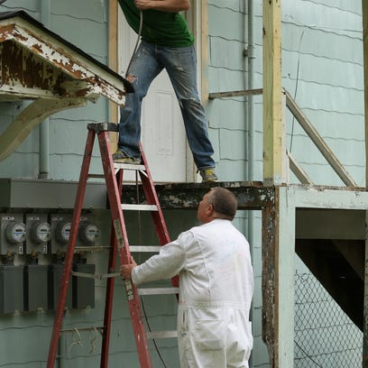 2 David Carothers spray paints the side of the house while Jeff Oakley stead.JPG