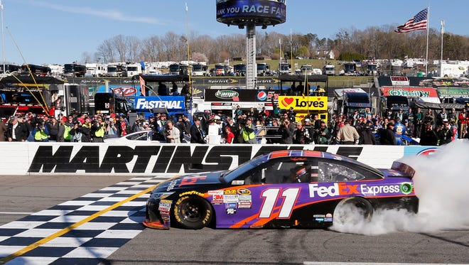 Denny Hamlin does a burnout after winning the NASCAR Sprint Cup Series auto race at Martinsville Speedway in Martinsville, Va., Sunday, March 29, 2015. (AP Photo/Steve Helber)
