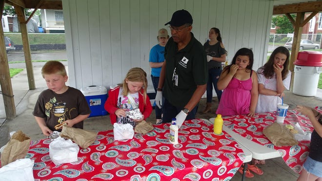 William Johnson, co-chairman of the Coshocton County Fatherhood Initiative, helps distribute free lunches to Coshocton children at Himebaugh Park.